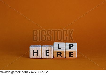 Help Is Here Symbol. Turned Wooden Cubes And Changed The Word Help To Here. Beautiful Orange Backgro