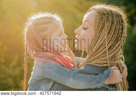 Family And Motherhood Concept. Mother And Child Girl Playing Kissing And Hugging. Little Daughter Hu