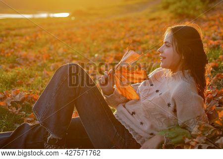 Woman Pretty Girl Enjoy Autumn. Girl Relaxed Lay Fallen Leaves On Sunny Autumn Day. Warmth And Cozin