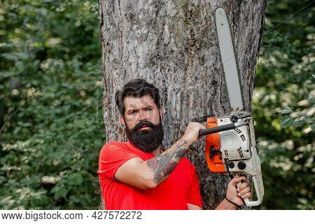 Professional Lumberjack Holding Chainsaw In The Forest. Woodcutter With Axe Or Chainsaw In The Summe