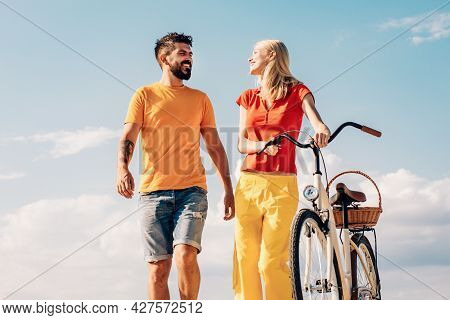Couple In Summer Dress Rides A Bike. Leisure And Lifestyle Concept. Active People. Enjoying Time Tog