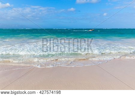 Small Motorboat Goes Along The Bavaro Beach, Coastal Landscape Of Dominican Republic On A Sunny Day