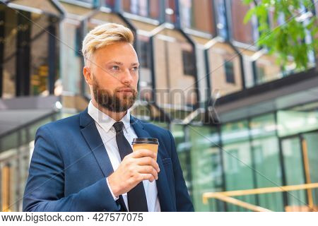 Confident businessman in front of modern office building. Financial investor is walking outdoor. Banking and business.