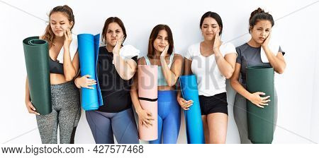 Group of women holding yoga mat standing over isolated background touching mouth with hand with painful expression because of toothache or dental illness on teeth. dentist concept.