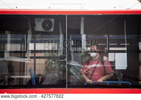 Belgrade, Serbia - July 4, 2021: Young Man At The Window Of A Bus From Gsp Beograd Wearing A Respira