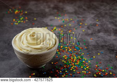 Butter Cream And Sugar Sprinkles In Bowl On Dark Background.