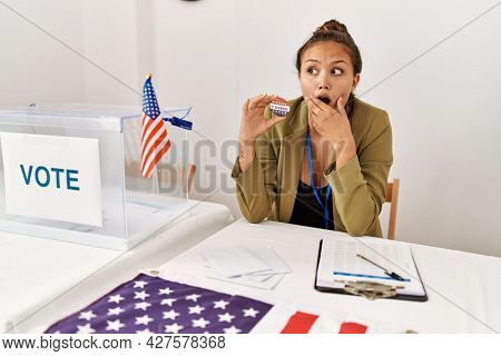 Beautiful hispanic woman at political campaign by voting ballot covering mouth with hand, shocked and afraid for mistake. surprised expression