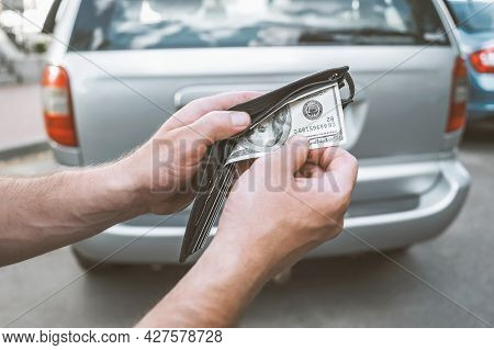 A Man Pulls Money Out Of A Purchase Wallet Of A Used Car