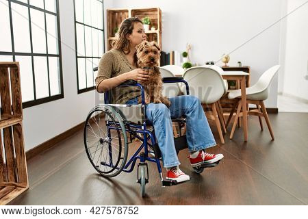 Young hispanic girl sitting on wheelchair at home shouting and screaming loud to side with hand on mouth. communication concept.