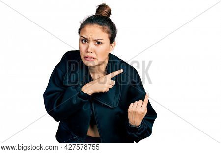 Young hispanic girl wearing sportswear pointing aside worried and nervous with both hands, concerned and surprised expression