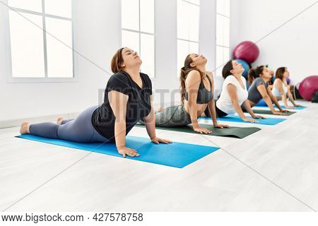 Group of young hispanic women concentrated training yoga at sport center.