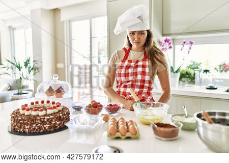 Beautiful young brunette pastry chef woman cooking pastries at the kitchen depressed and worry for distress, crying angry and afraid. sad expression.