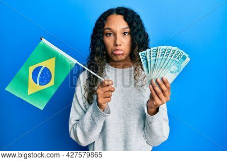 Young latin woman holding brazil flag and real banknotes depressed and worry for distress, crying angry and afraid. sad expression.