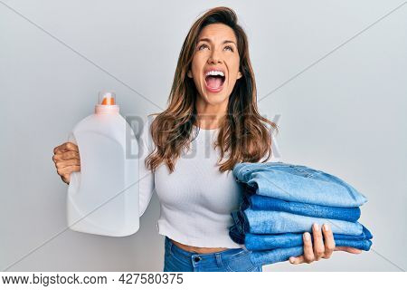 Young latin woman holding jeans for laundry and detergent bottle angry and mad screaming frustrated and furious, shouting with anger looking up.