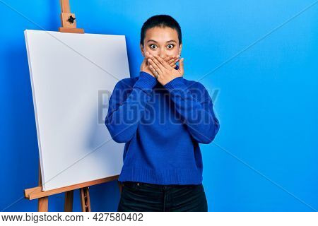 Beautiful hispanic woman with short hair standing by painter easel stand shocked covering mouth with hands for mistake. secret concept.