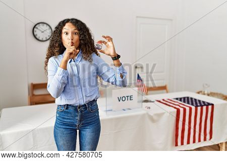 Beautiful hispanic woman standing by at political campaign by voting ballot asking to be quiet with finger on lips. silence and secret concept.