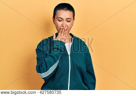 Beautiful hispanic woman with short hair wearing sporty jacket bored yawning tired covering mouth with hand. restless and sleepiness.