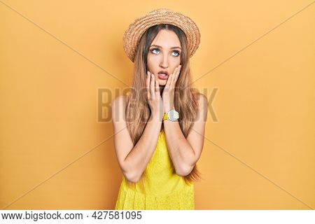 Young blonde girl wearing summer hat tired hands covering face, depression and sadness, upset and irritated for problem