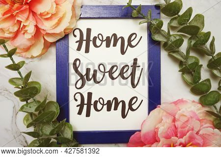 Home Sweet Home Written On Blue Frame With Green Leave And Pink Flower Flat Lay On Marble Background