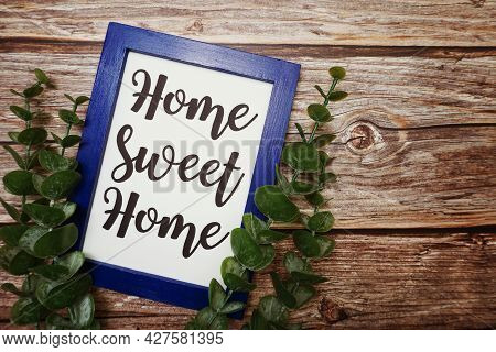 Home Sweet Home Written On Blue Frame With Green Leave Flat Lay On Wooden Background