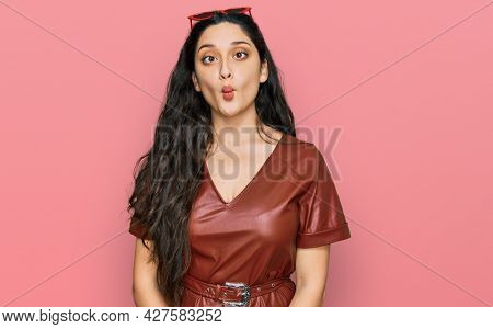 Brunette young woman wearing dress and sunglasses making fish face with lips, crazy and comical gesture. funny expression.
