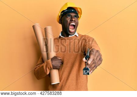 Young african american man wearing safety helmet holding blueprints and new home key angry and mad screaming frustrated and furious, shouting with anger looking up.