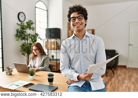 Business manager smiling happy and confident. Employee working at the office.