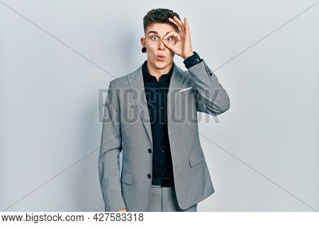 Young caucasian boy with ears dilation wearing business jacket doing ok gesture shocked with surprised face, eye looking through fingers. unbelieving expression.