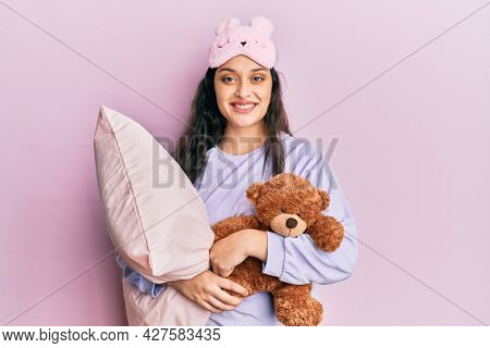 Beautiful middle eastern woman wearing sleep mask hugging pillow smiling with a happy and cool smile on face. showing teeth.