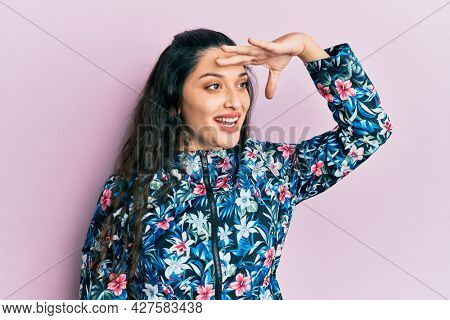 Beautiful middle eastern woman wearing casual floral jacket very happy and smiling looking far away with hand over head. searching concept.