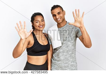 Young latin couple wearing sportswear standing over isolated background showing and pointing up with fingers number ten while smiling confident and happy.