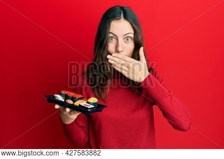 Young brunette woman showing a plate of sushi covering mouth with hand, shocked and afraid for mistake. surprised expression