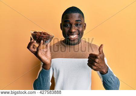 Young african american man holding bowl with raisins smiling happy and positive, thumb up doing excellent and approval sign