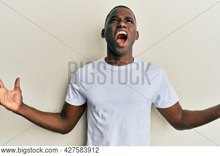 Young african american man wearing casual white t shirt crazy and mad shouting and yelling with aggressive expression and arms raised. frustration concept.