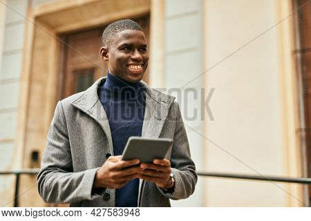 Young african american man smiling happy using touchpad at the city