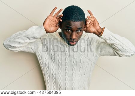 Young african american man wearing casual clothes trying to hear both hands on ear gesture, curious for gossip. hearing problem, deaf
