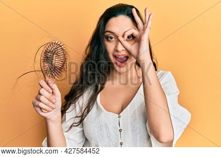 Beautiful middle eastern woman holding comb loosing hair smiling happy doing ok sign with hand on eye looking through fingers