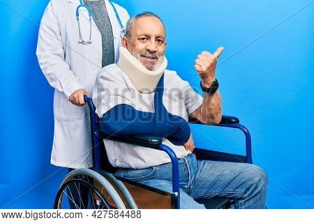 Handsome senior man with beard sitting on wheelchair with neck collar pointing to the back behind with hand and thumbs up, smiling confident