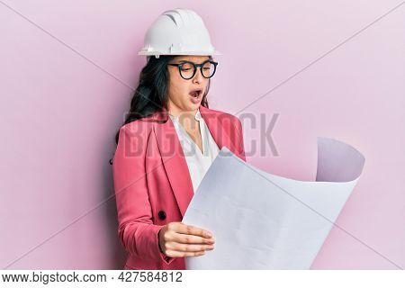 Beautiful middle eastern woman looking at paper blueprints wearing safety helmet angry and mad screaming frustrated and furious, shouting with anger. rage and aggressive concept.