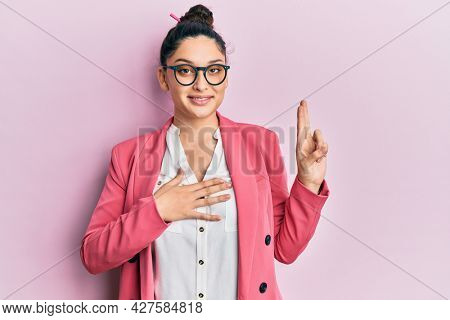 Beautiful middle eastern woman wearing business jacket and glasses smiling swearing with hand on chest and fingers up, making a loyalty promise oath