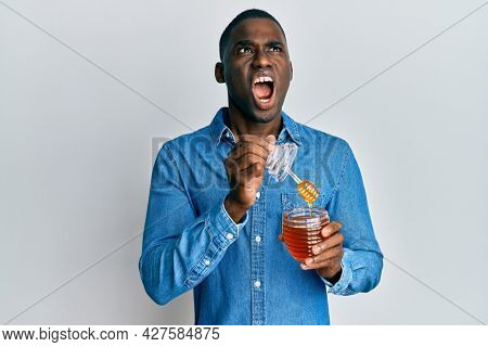 Young african american man holding honey angry and mad screaming frustrated and furious, shouting with anger looking up.