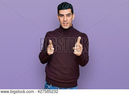 Handsome hispanic man wearing casual turtleneck sweater pointing fingers to camera with happy and funny face. good energy and vibes.