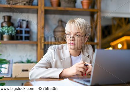 Photo Of A Pensive Woman In Front Of A Laptop Monitor. She Works With Documents And Papers At Home -