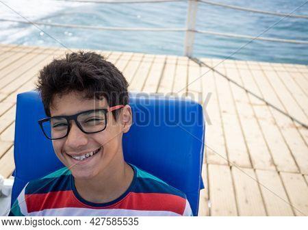 Teenage boy sitting on pier chair and enjoying