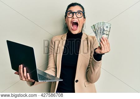 Young hispanic woman wearing business style holding laptop and 50 euros angry and mad screaming frustrated and furious, shouting with anger looking up.