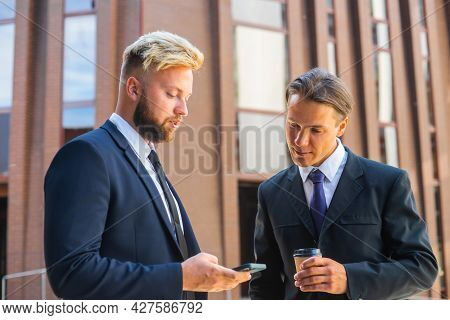 Confident Businessman And His Colleague Are Using Smartphone In Front Of Modern Office Building. Fin