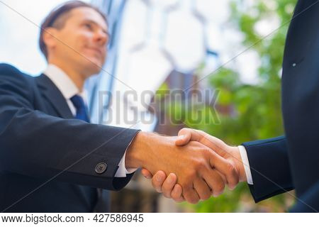 Handshake Close-up. Businessman And His Colleague Are Shaking Hands In Front Of Modern Office Buildi