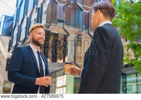 Confident Businessman And His Colleague In Front Of Modern Office Building. Financial Investors Are