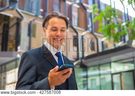 Confident Businessman In Front Of Modern Office Building. Financial Investor Is Using Smartphone Out