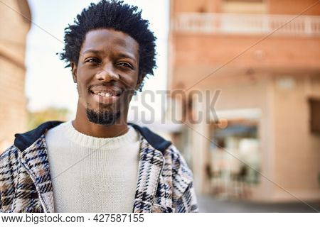 Handsome black man with afro hair and beard smiling happy outdoors